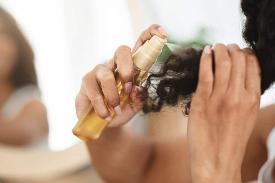 Girl putting coconut oil in her hair
